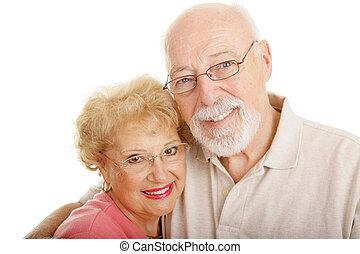 Senior couple wearing glasses. White background.