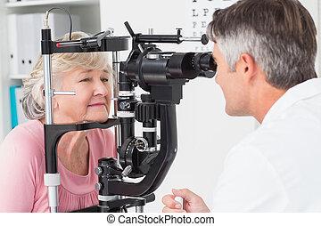 Optician examining senior female patient through slit lamp...