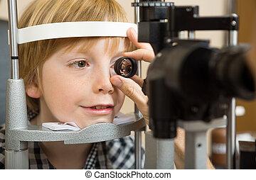 optician, main, vérification, garçon, oeil, à, lentille