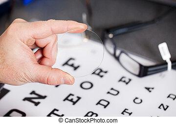 Optician's Hand Holding Lens Against Snellen Chart