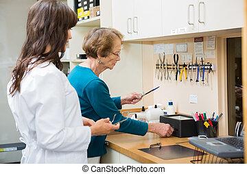 optiker, mit, lehrling, reparatur, brille, in, werkstatt