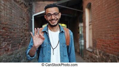 Optimistic African American guy showing OK gesture smiling ...