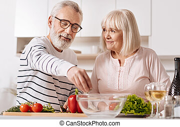 Optimistic aged couple cooking together in the kitchen