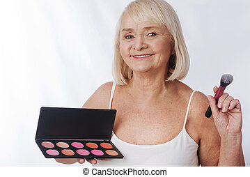 Optimistic aged woman using a rouge palette