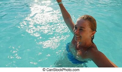 Optimistic blond woman smiling and swimming in a pond on a...