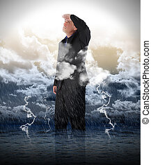 A business man is looking up to bright light in stormy weather for a strength, success or faith metaphore.