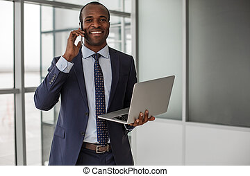 Optimistic businessman is having pleasant communication on mobile phone