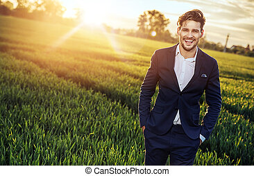 Optimistic businessman relaxing on the wheat field