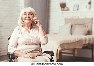 Optimistic disabled aged woman using phone at home