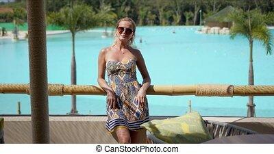 Optimistic female resting on balcony near swimming pool - ...