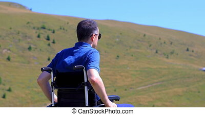 Optimistic handicapped man sitting on wheelchair raising his hands and admiring nature on the mountain. Travel and freedom concept. Hand held shot