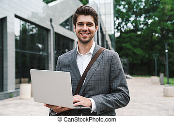 Optimistic handsome business man using laptop - Image of ...
