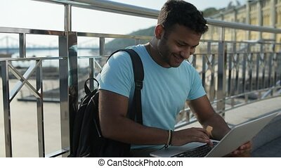 Optimistic handsome man using the laptop - Leisure time....