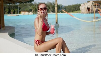 Optimistic lady enjoying drink on poolside - Side view of ...