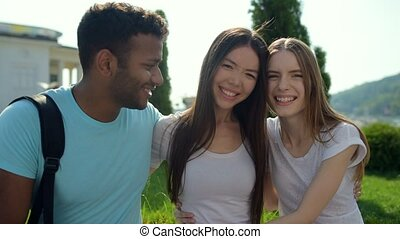 Optimistic light-hearted friends hugging and smiling -...