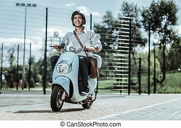 Optimistic male student capping to university on motorbike -...