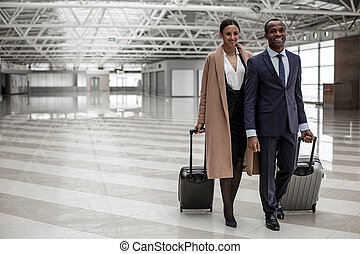 Optimistic man and woman are going together with suitcases
