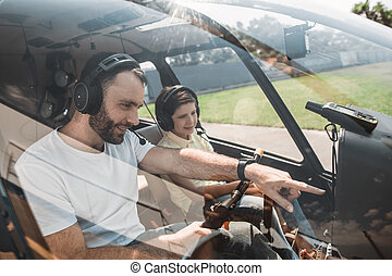 Optimistic man telling with child in helicopter