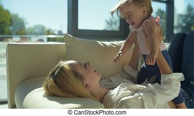 Optimistic mother playing with cute little daughter