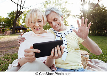 Optimistic old couple using tablet in the park