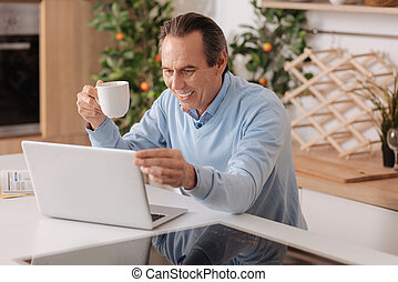 Optimistic pensioner using modern gadget at home