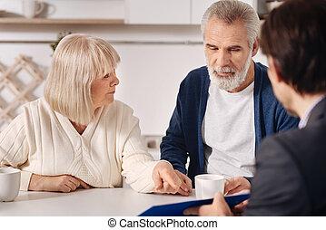Optimistic senior couple having conversation with advisor at home