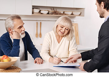 Optimistic senior couple signing documents at home