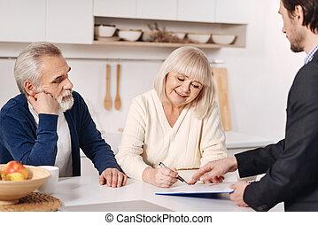 Optimistic senior couple signing documents at home