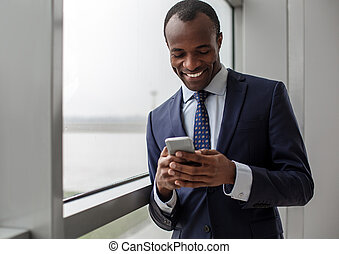 Optimistic stylish businessman is using his smartphone -...