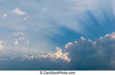 Optimistic sunset rays behind the clouds. Glow in the sky. Symbol of light. Beautiful scene of nature.