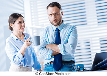 Optimistic woman giving a gloomy man a cup of tea and smiling
