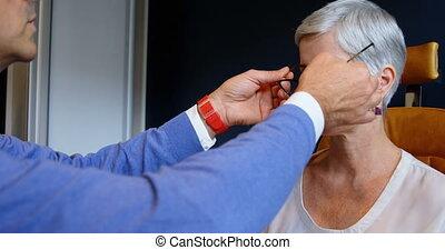 Optometrist adjusting eyeglasses on patient eyes 4k