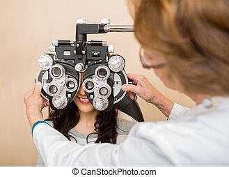 Optometrist Adjusting Phoropter For Patient