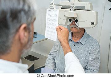 optometrist adjusting phoropter for senior male patient