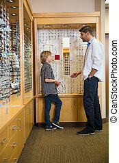 Optometrist And Boy Communicating In Store