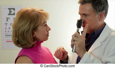 Optometrist checking his patient - An optometrist using an...