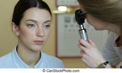 Optometrist checking patient eyes with retinoscope - Serious...