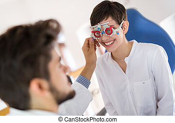 optometrist checking patient eyesight and vision correction...