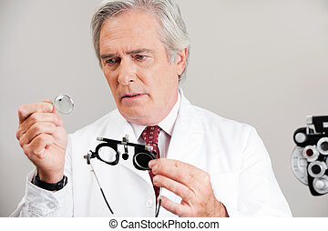 Optometrist Checking the Lens Of Trial Frame - Skilled...