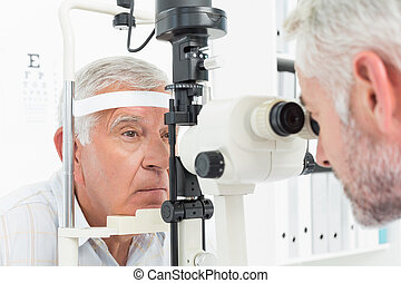 Optometrist doing sight testing for senior patient - Close-...
