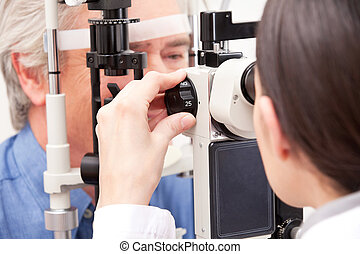 Optometrist doing sight testing for pateient.