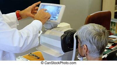 Optometrist examining patient eyes with autorefractors 4k