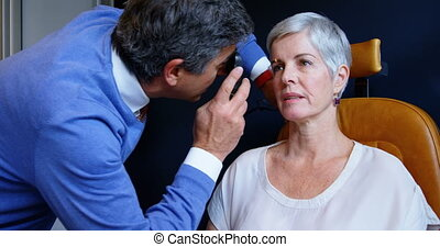 Optometrist examining patient eyes with ophthalmoscope 4k