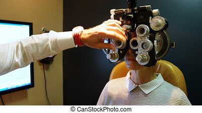 Optometrist examining patient eyes with phoropter 4k