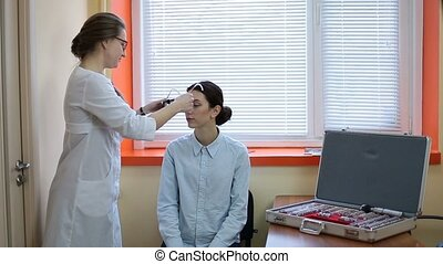 Optometrist examining patient with trial frame
