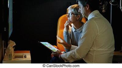 Optometrist explaining eyesight report over digital tablet 4k