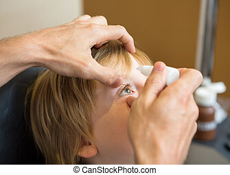 Optometrist Hands Putting Eye Drops In Patients Eye -...