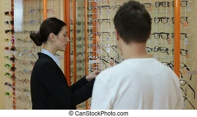 Optometrist helping client to choose eyeglasses - Smiling...