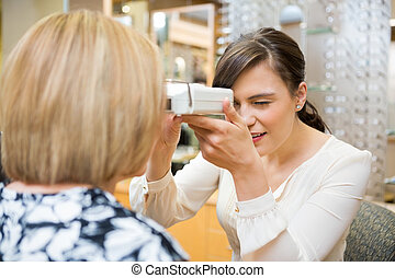 Optometrist Measuring Pupilary Distance - Female optometrist...
