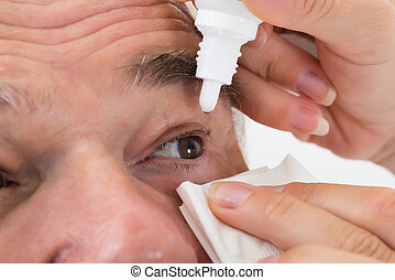Optometrist Putting Eye Drops In Patient's Eye